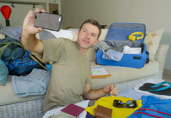 young happy and excited man taking selfie portrait with mobile phone camera while packing travel suitcase and preparing mess clothes and stuff