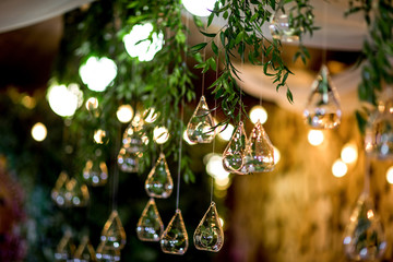 Yellow lamps hang from green garland on the ceiling
