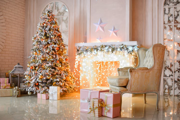 White fireplace decorated with yellow garland and Christmas tree standing by it