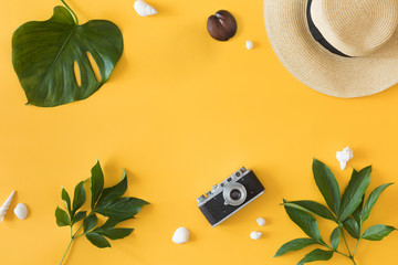 Top view and flat lay of yellow background for summer vacation, photo camera, hat, palm leaf. Copy space.
