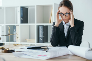 financier working at table in office and having headache