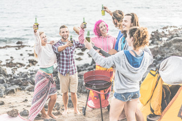 Group of happy friends making barbecue party on the beach