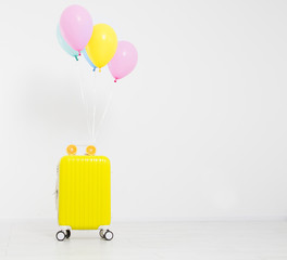 Colorful balloons and suitcase isolated on white background.Holidays concept. Copy space