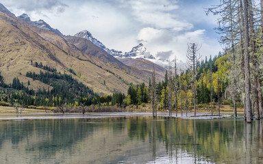 """Landscapes of snow mountains, forest, and peaceful lake, in """"Four Girls Mountain"""", sichuan, China."""