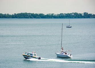 water police patrols Zemplinska Sirava lake, Slovakia. two sailboats stand still, safe vacation in summer