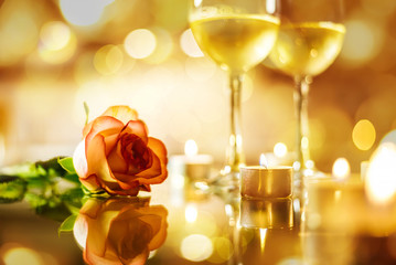 Two glasses with white wine and rose flower on bokeh background. Romantic concept.