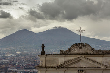 Old italian church with mount Vesuvius at backgound at cloudy day in Naples, Italy