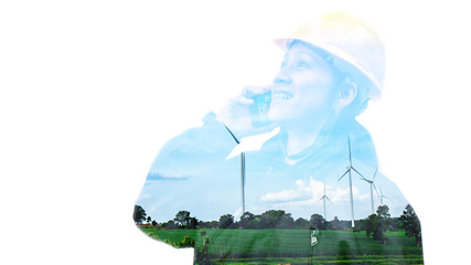 Double exposure of engineer using tablet with wind turbine