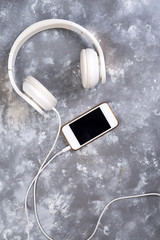 Headset and a phone on a stone background. Ready to listen to music.