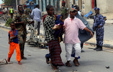 Civilians carry an unidentified woman injured from the scene of a suicide car bombing near Somalia's presidential palace in Mogadishu