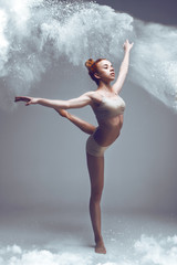 Dancing in flour concept. Redhead sporty performer woman in dust / fog. Girl wearing white top and shorts making dance element in flour cloud on isolated background