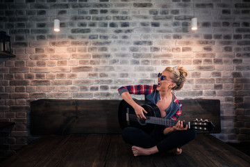 Beautiful blonde girl in causal clothes playing music on guitar and singing in stylish apartment. Unusual young woman spend time at modern home.