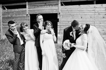 Bridesmaids with groomsmen and wedding couple having fun outdoors next to the old rustic wooden barn. Black and white photo.