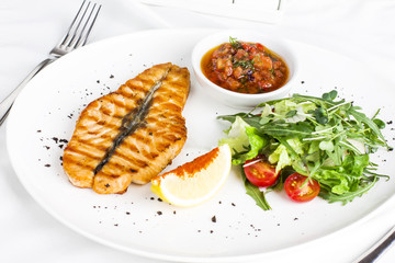 The large salmon steak red fish on the grill with lemon, sauce with vegetables and greens on white plate
