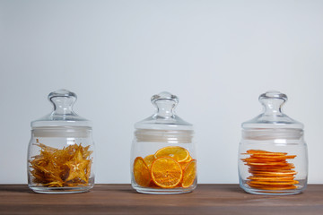 Fruit chips in a glass jars on the wooden table