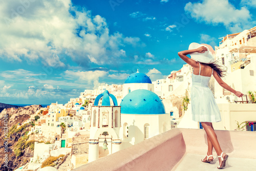 Wall mural Travel Santorini luxury cruise vacation woman tourist looking at famous Europe destination - Sun summer holiday lifestyle.