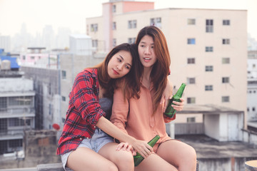 Two asian women drinking at rooftop party, outdoors celebration, LGBT couple