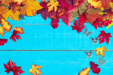 Blank antique rustic teal blue background with colorful autumn leaves and butterflies border; wooden fall sign with copy space