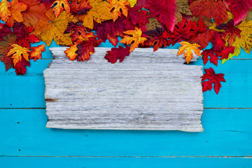 Blank rustic sign with colorful autumn leaves border hanging on antique rustic teal blue wood background; seasonal background with copy space