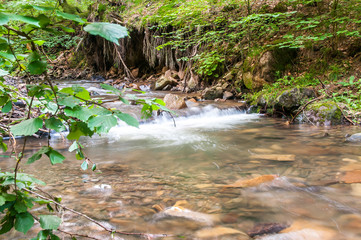 Crystal clean little creek , small waterfall scenic view on the Carpathian mountains.
