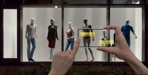 Augmented reality marketing concept. Hand holding digital tablet smart phone use AR application to check special sale price in retail fashion shop, mall interior design