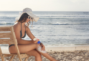 Young woman applying sunscreen at beach. Healthcare concept