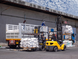 The truck delivery sugar in bag to  store in warehouse by labor and  forklift