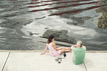 Pareja caucásica disfrutando de un descanso tranquilamente junto a un río en la ciudad