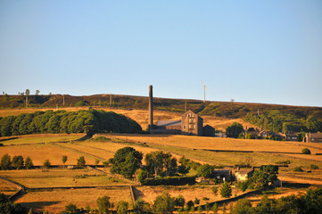 a panoramic view of the village of old town near hebden bridge in west yorkshire with summer sunshine on farms and old mill buildings with midgley moor at the top of the hills