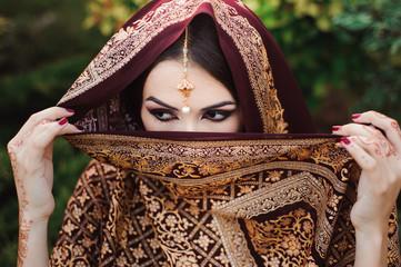 Portrait of beautiful indian girl . Young hindu woman model with tatoo mehndi and kundan jewelry.