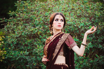 Beautiful young caucasian woman in traditional indian clothing sari with bridal makeup and jewelry and henna tattoo on hands