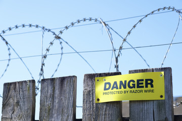 Razor wire fence protection danger sign on fence