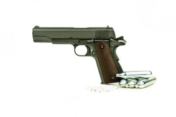 Profile view of isolated semi-automatic airsoft handgun with bullets and gas container. Replica of real handgun on white background.