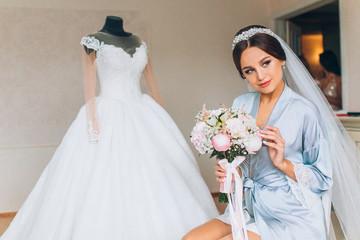Beautiful happy brunette bride in a stylish robe posing near manequin wedding dress, morning wedding preparation concept, bride portrait face closeup.