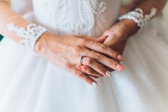 The hands of the bride wearing and corrects a gold wedding engagement ring with a diamond. Bride's Preparations. Wedding Morning. Jewelry. Manicure close up.