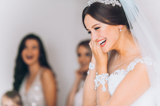 Happy bridesmaid hugging the bride in the bedroom in the morning. Before wedding ceremony. Bride preparing and wait groom.