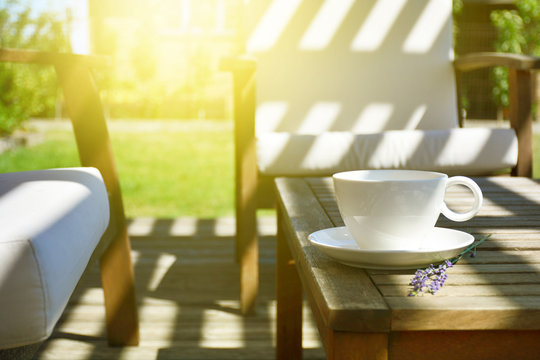 Cup of tea served on natural wood table in the provence style backyard garden terrace