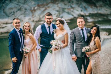Wedding day bride and groom with bridesmaids and groomsmen posing in sunlight evening in mountains near river gorgeous wedding newlyweds couple with best friends.  People drink champagne and hugging.