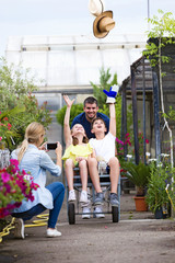 Happy father with his son and daughter playing with a wheelbarrow while mother taking a photograph in the greenhouse.