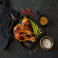 Grilled chicken drumsticks and asparagus on ceramic pan