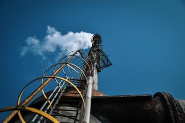 Au pied de la torche en sommeil d'une plateforme industrielle sur fond de ciel bleu