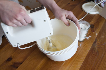 Woman hands whisking the pastry by mixer