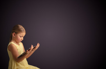 Adorable little girl using tablet with dark empty space
