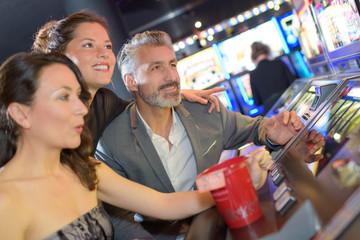 three adults sat excitedly around casino machine