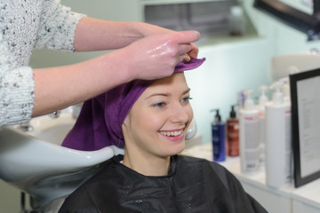 young smilingwoman having hair washed by stylist in salon sink