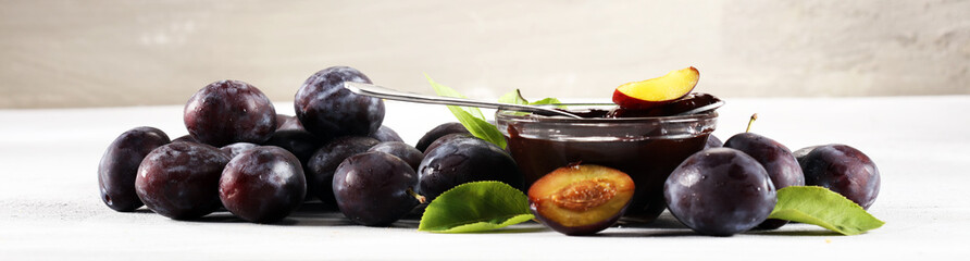 Sweet homemade plum jam and fruits on a stone table.