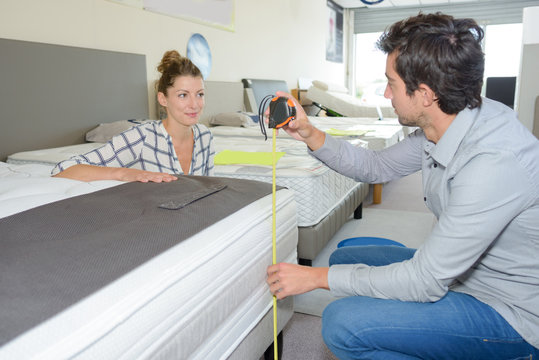 couple in furniture store measuring bed