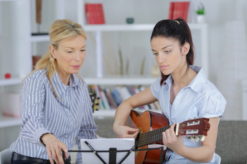 lady music professor teaching guitar to her young student