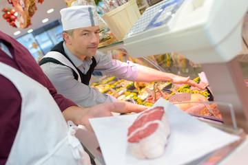 Butcher serving meat