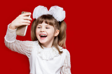 Cute little girl in white bows hold telephone and take picture on red background. Communication concept